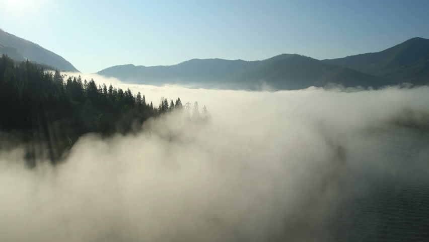 Aerial View. Flying over the high mountains in beautiful clouds . Aerial camera shot.  Air clouds. Altai, Siberia.
