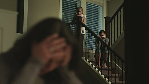 A sad mother sits at the table while her daughters look at her from the stairs. Medium to close up shot.