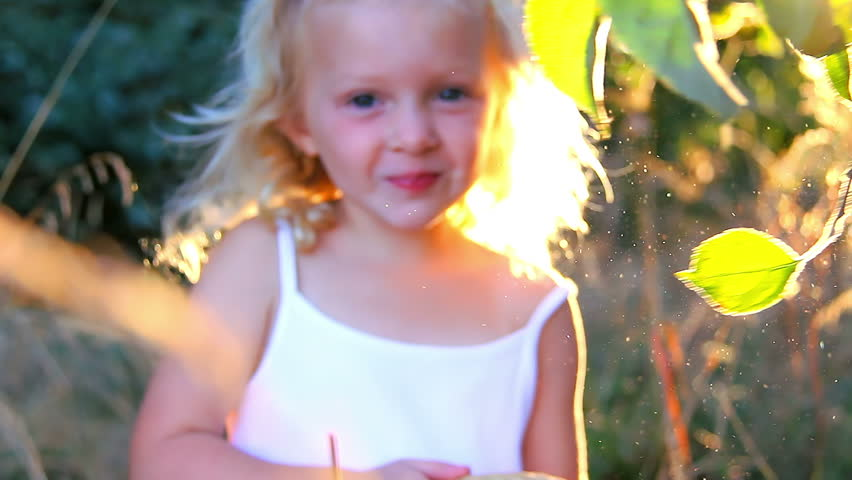 An adorable little girl smiles as she picks an apple off an apple tree. Close up shot.