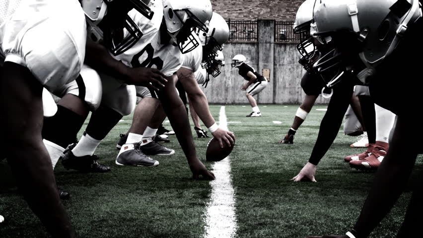 The defensive and offensive lines of two football teams meet at the line of scrimmage. High contrast, with camera flashes and time remap. | Shutterstock Video #4681844