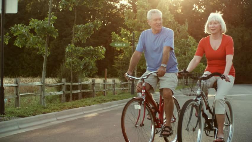 Happy senior couple ride bikes down the street. Wide shot.