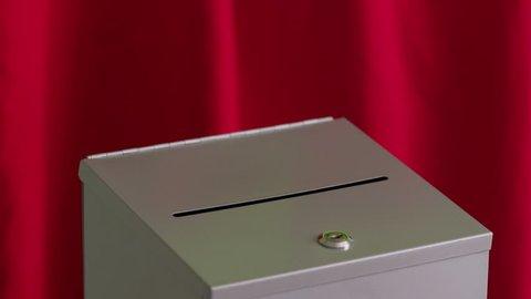 Hand puts vote into ballot box