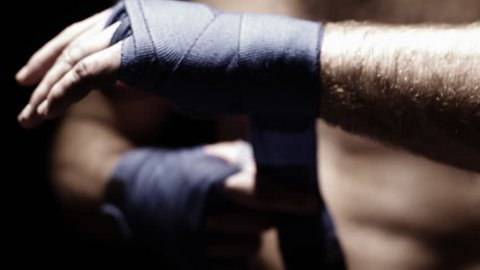 Mixed martial arts athlete wraps his hand with blue cloth. Close up shot.