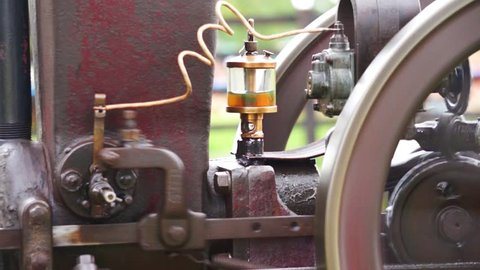 Close up view of a vintage stationary engine, showing the flywheel and oil reservoir.