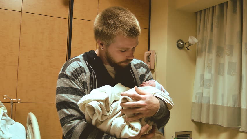 A new father holds his newborn infant for the very first time in a hospital