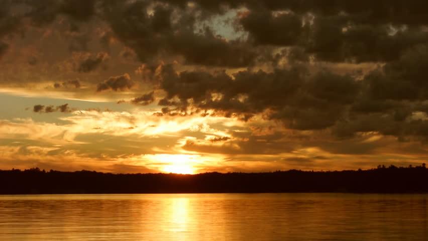 Timelapse of golden sunset. Motorboat crosses path of sun's reflection. Muskoka, Ontario, Canada.