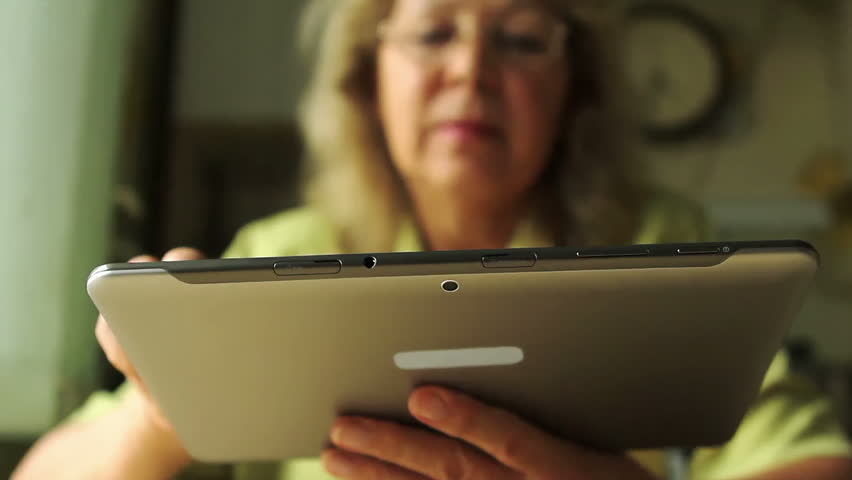 Portrait of a woman at the age of looking through the information on the Tablet PC