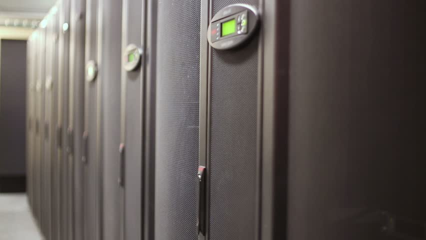 Engineer unlocks door of server rack with many hard drives and control panel