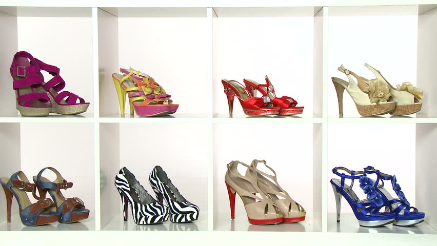 Beautiful woman choosing shoes in her closet. High definition video shot on white studio background.