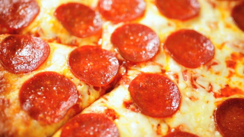Close up removing a delicious slice of home baked pepperoni cheese pizza