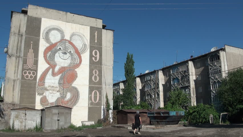 OSH, KYRGYZSTAN - 30 JUNE 2013: People walk past an old Soviet apartment building, with an advertisement of the 1980 Olympic Games on it, in Osh, Kyrgyzstan