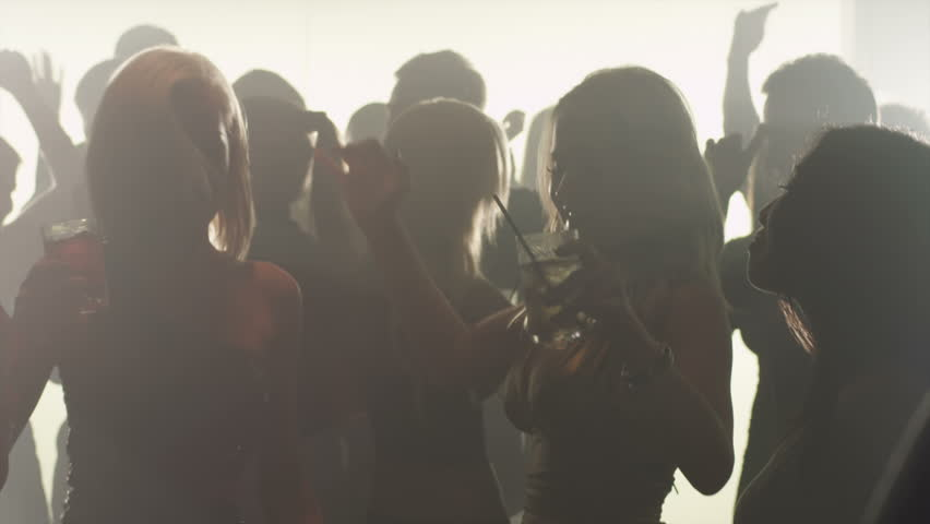 A group of attractive silhouetted young adults dance in a smokey club in slow motion #4776851