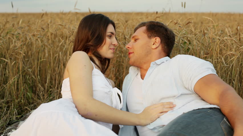 Charming couple flirting and cuddling in the field - HD stock video clip