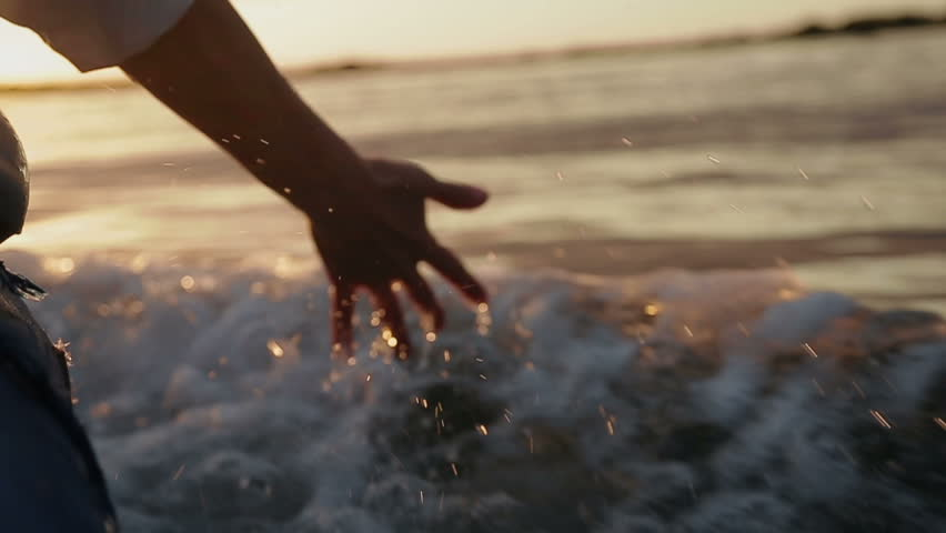 Hand glides over waves at sunset | Shutterstock HD Video #4780511