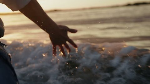 Hand glides over waves at sunset