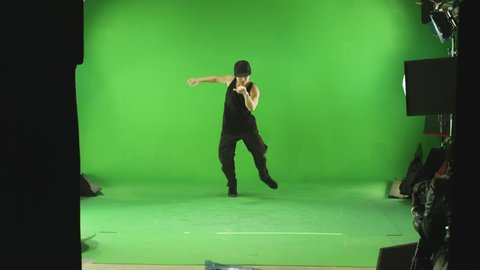 A lone male dancer on a green screen stage