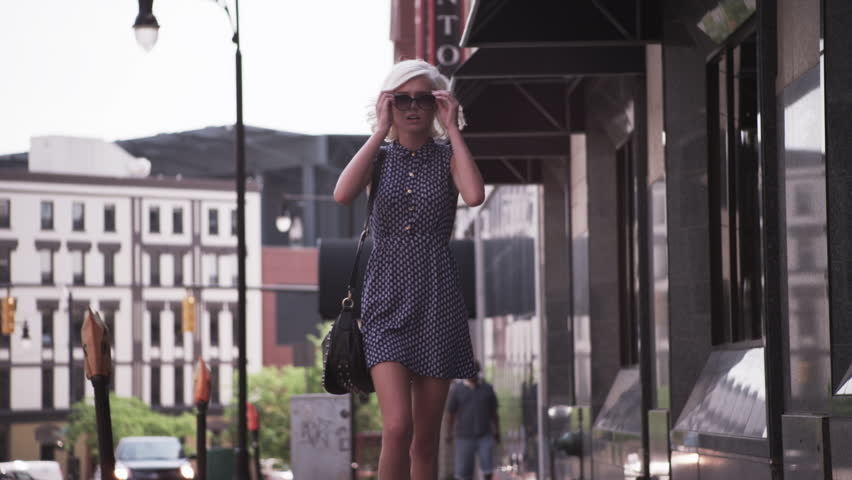 woman walks puts on sunglasses in the city slow  motion