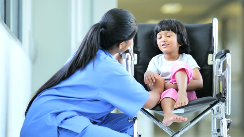 Devoted female medical aide reassuring little Indian child patient in wheelchair waiting for hospital treatment