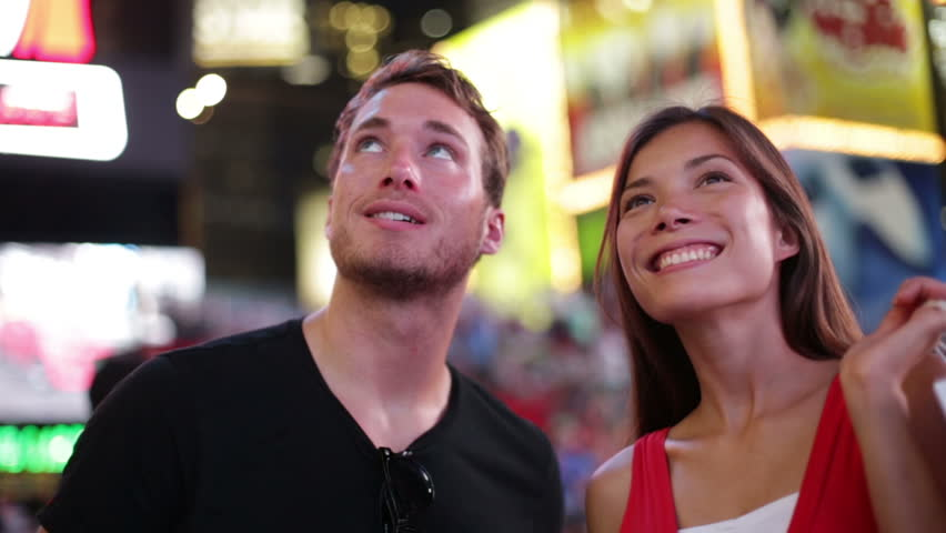 People in New York - happy couple on Times Square. Shopping dating young couple in love. Beautiful young multiracial tourists having fun date in city, Manhattan, USA. Asian woman, Caucasian man.