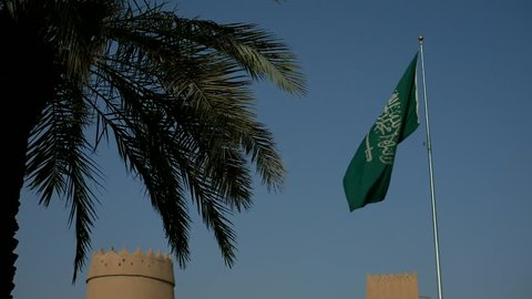 Scene of real flag of Saudi Arabia with a dates palm tree and fortress tower. Video can be used for oil, historical, tourism, political and islamic themes.