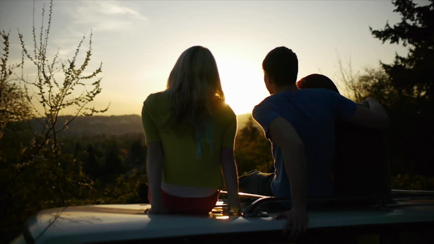 A Couple Enjoy The Sunset With Their Friend