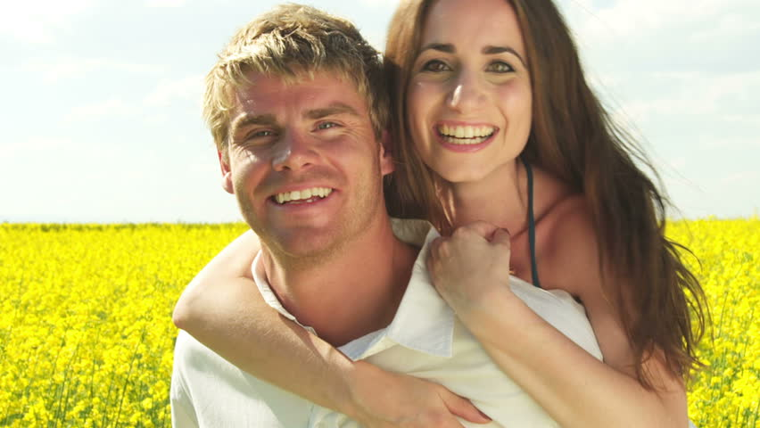A young holds his girlfriend on his back as they stand in a wide open yellow field and smile into the camera on a sunny day   Shutterstock HD Video #4840811