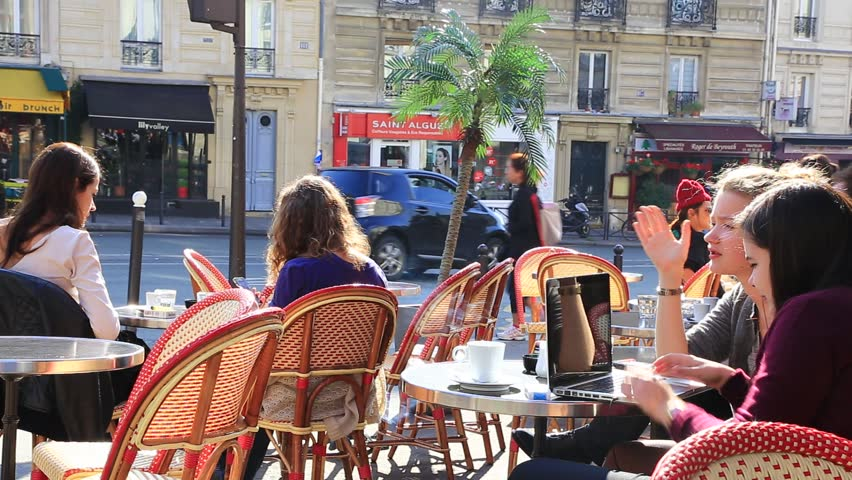 PARIS, FRANCE - OCTOBER 7 : Two teen-age girls playing with computer in the open street café in Paris, rue Monge. Other two girls talking on the background on October 7th 2013 in Paris, France