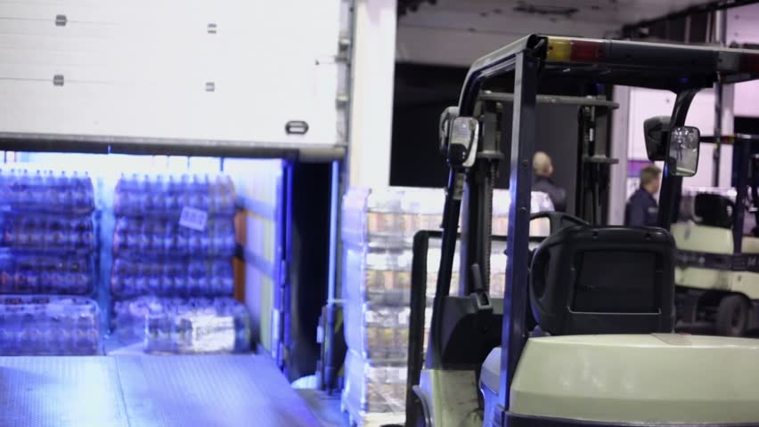 Warehouse gates close after loading of trucks by bottles of beer