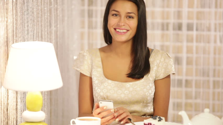 Pretty girl sitting at cafe with cup of tea and piece of cake using cellphone looking at camera and smiling. Panning camera