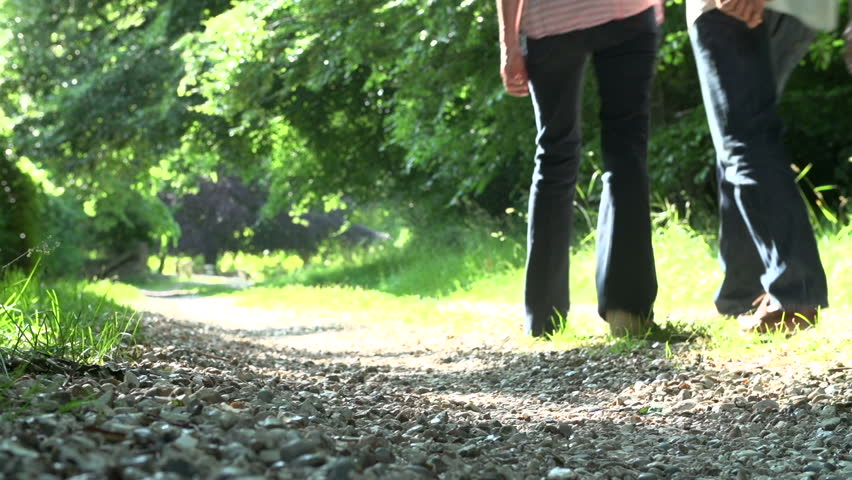Middle aged couple walking along rural country path together holding hands | Shutterstock HD Video #4878851