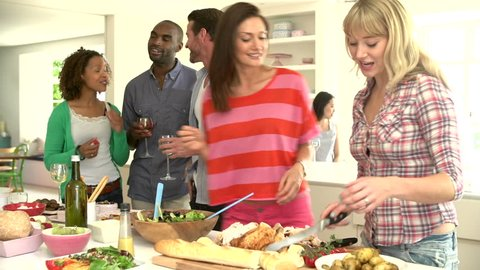 Group of friends eating, talking, and drinking in kitchen before a delicious buffet at a dinner party