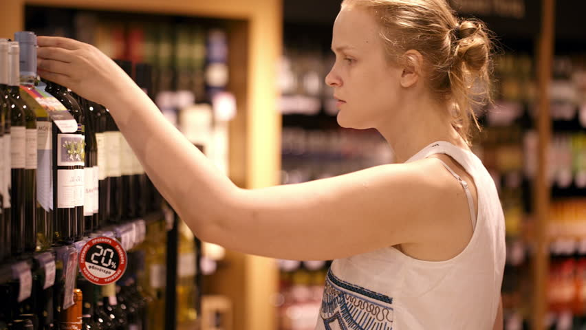 Woman shopping for wine or other alcohol in a bottle store standing in front of shelves full of bottles with a serious expression as she tries to make up her mind