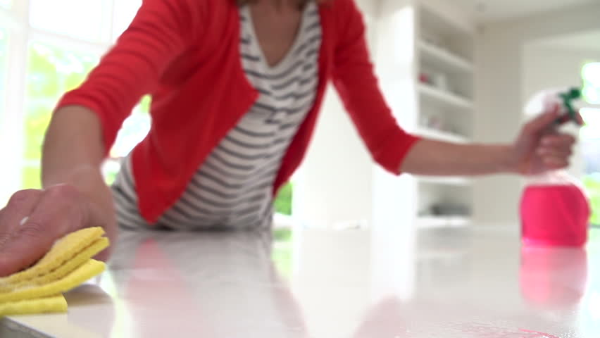 Slow motion close up view of woman cleaning kitchen counter with disinfectant spray