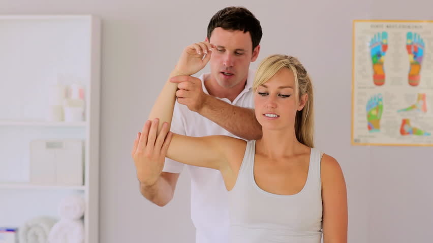 Physiotherapist manipulating patients arm while chatting in his office