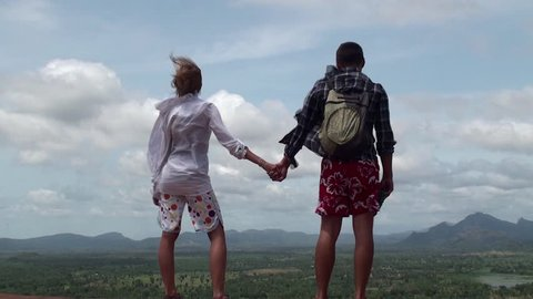 Young couple of tourists stands in the wind on top of a mountain.