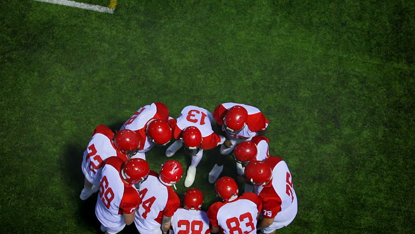 A birds eye view of a football team discussing the next play while in a huddle