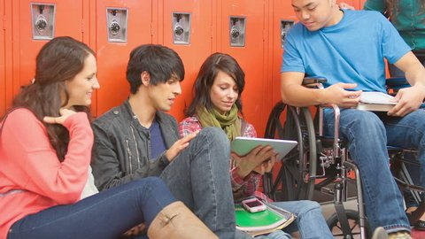 A group of friends sit next to their lockers and hang out while looking at a tablet before class