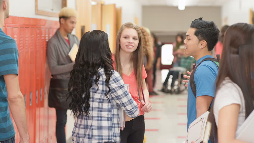 a group of friends stand in the hallway and talk and laugh