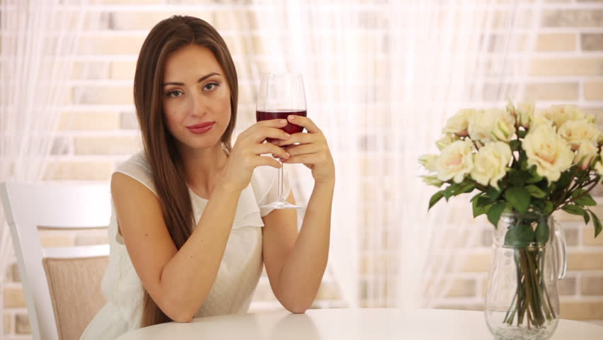Beautiful woman sitting at cafe drinking wine looking at camera and smiling