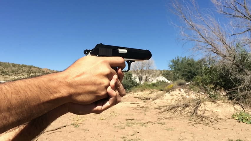 A man shoots a pistol in the desert.  Shot in super slow motion 120fps.