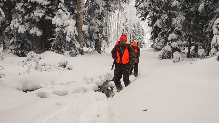 Elk hunters hiking through deep snow in northern Colorado wilderness after an