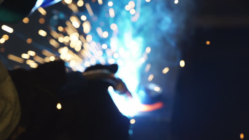 Workers grinding and welding in a factory. Welding on an industrial plant. Slow motion.