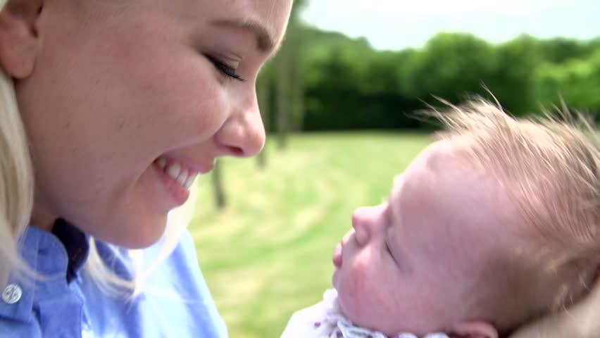 Mother kisses sleeping newborn baby in garden