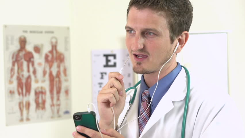 Young doctor dictating notes to cell phone recorder