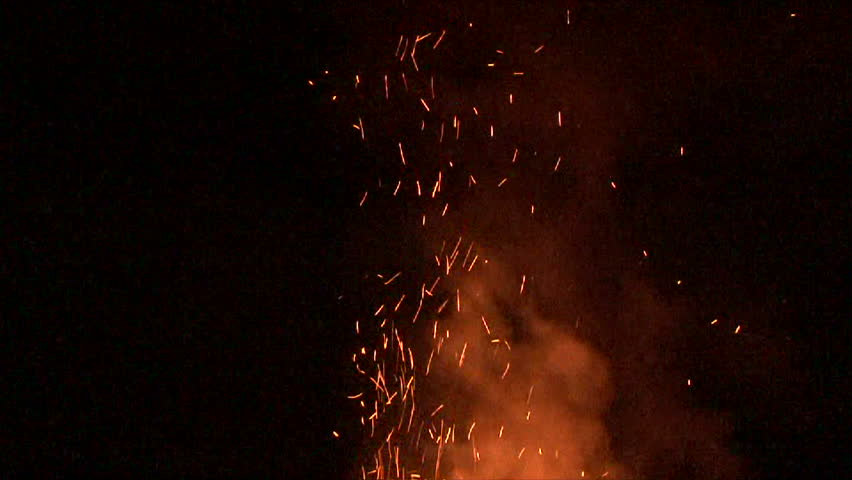 Large fire burning at night with smoke and sparks rising.