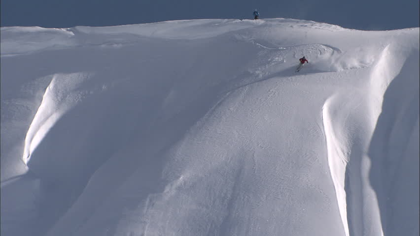 Skier charging down a perfect powder covered face with a bluebird sky, drops a cliff and nearly falls but holds it together.