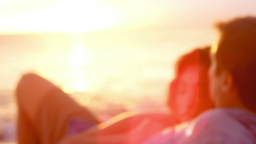 A young man and woman lay in the sand at the beach and look out to the ocean, with lens flare | Shutterstock HD Video #4941488
