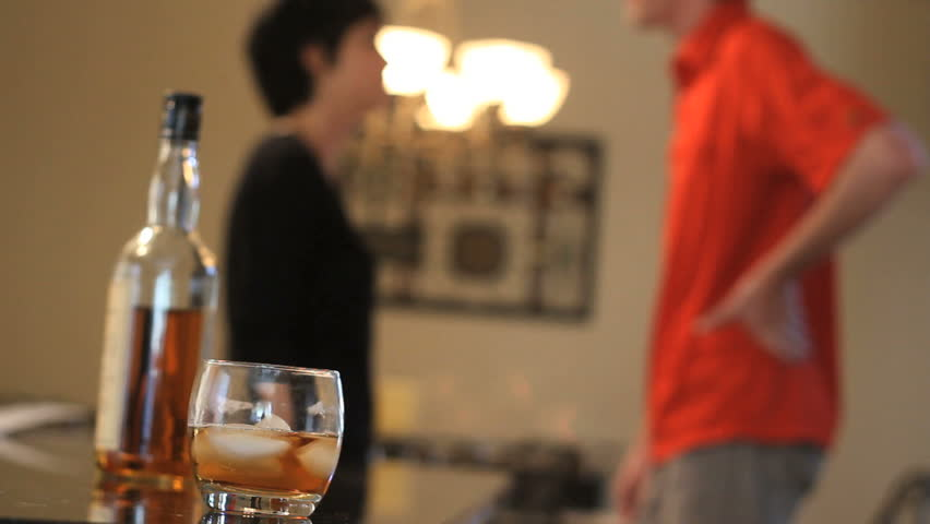 A young couple fights, ending with the woman aggressively pushing her partner away. Alcohol in focus foreground with couple in back.
