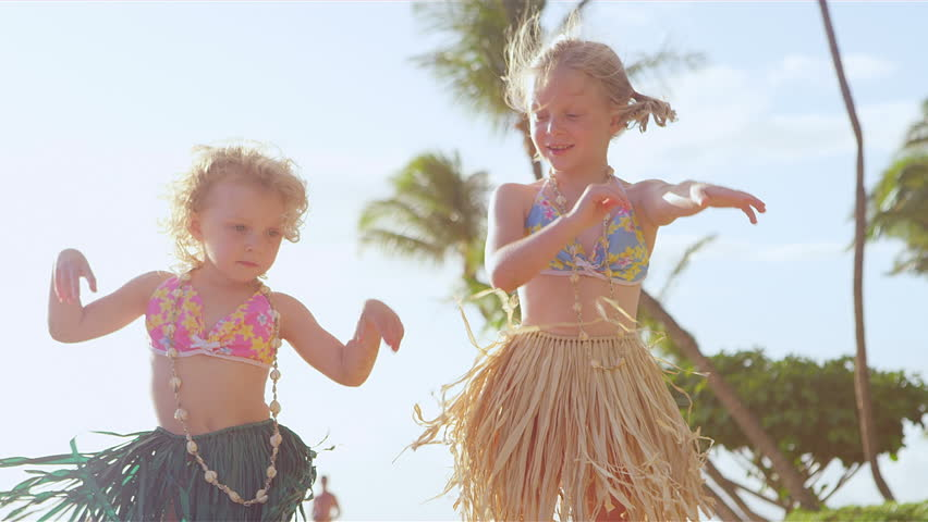 Two young sisters stand in front of the camera and show off their hula dance moves. Medium shot.