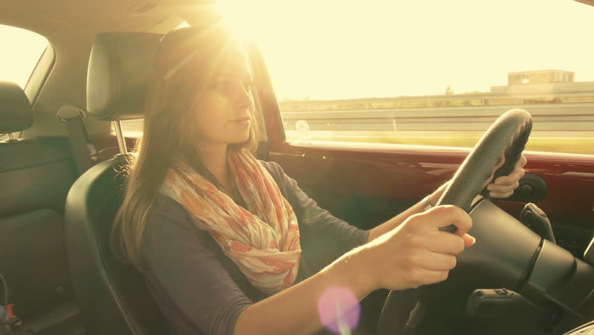 Brunette girl driving a car, gorgeous sun flare and grading. Occasional exposure variations are caused by the road signs blinding the sun for a second | Shutterstock HD Video #4961387